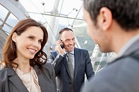 Germany, Leipzig, Business people smiling, businessman with cell phone in background