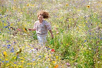 Girl holding sunflower running through field of wildflowers