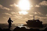 Fisherman and ship wreck at sunset, Cape Agulhas, Western Cape, South Africa