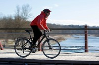 Germany, Bavaria, Munich, Mid adult woman riding bicycle