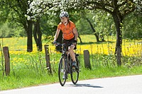 Germany, Bavaria, Young woman riding bicycle