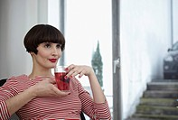 Germany, Cologne, Young woman sitting with glass of tea in apartment