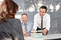 Germany, Leipzig, Business people discussing about architectural model, smiling