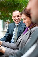 Germany, Leipzig, Business people sitting on bench, smiling (thumbnail)
