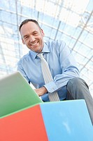 Germany, Leipzig, Businessman using laptop with cubes, portrait (thumbnail)