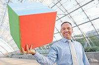 Germany, Leipzig, Businessman holding cube, smiling