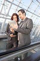 Germany, Leipzig, Business people using digital tablet on escalator