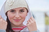 Close up portrait of teenage girl wearing knit hat and hood