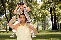Caucasian man carrying son on shoulders in park
