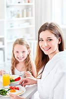 A mother and child have breakfast in the kitchen