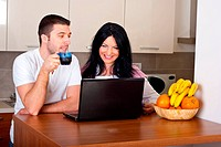 Cheerful couple drinking coffee using laptop and having funny conversation in the morning in their kitchen