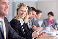 Portrait of confident businesswoman holding report in conference room with co_workers