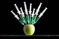 Syringes stuck in apple