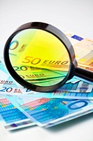 Small heap of Euro currency under a magnifying glass,