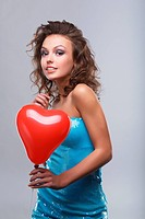 Close_up of a young, beautiful, brown_haired woman with red balloon.