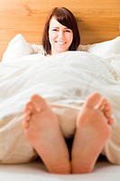 Young woman in her bed with feet outside the blanket