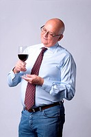 portrait of a successful senior man with glass of wine on gray background
