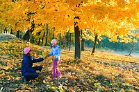 Happy family mother with daughter walking in golden maple autumn park