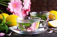glass cups of mint tea with lemons and gerbera flowers as decoration on old rustic table