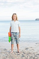 Spain, Mallorca, Boy with water gun on beach, portrait
