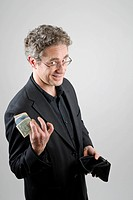 Businessman wearing a black suit holding money in his hand