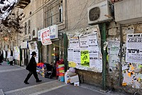 Wall newspapers and an Orthodox Jew in the district of Me'a She'arim or Mea Shearim, Jerusalem, Israel, Middle East