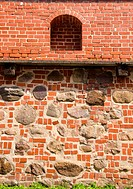 Architectural defence wall background. Ancient wall made of red brick and stones.