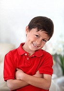 Happy cheerful young Latino or Hispanic boy in red shirt against light background in portrait mode with copy space on top