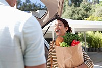 Woman unloading groceries from car