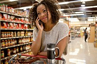 Woman talking on cell phone in supermarket (thumbnail)