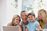 Family using laptop together in home (thumbnail)