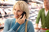 Older woman on cell phone in supermarket (thumbnail)