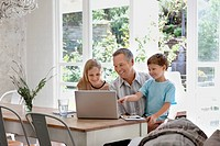 Family using laptop together at dining room table