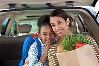 Mother and daughter unloading groceries from car