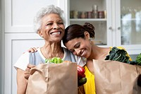 Mother and daughter unpacking groceries in kitchen
