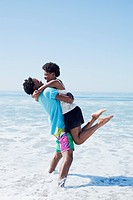 Couple hugging in waves at beach
