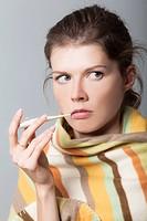 giovane donna con coperta e termometro