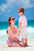 Happy mother and son at tropical beach playing together