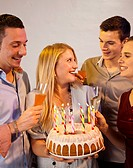 Group of young people celebrating with birthday cake