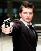 A bussiness man with a gun. The focus is on the hand and gun