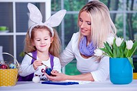a girl painting the easter eggs with her mother