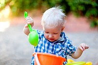 adorable toddler playing with shovel and bucket in sand