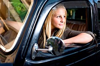 Beautiful young blond girl in a black vintage car, looking away.