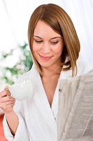 Breakfast _ happy woman reading newspaper drink coffee, wearing bathrobe