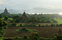 Rising smoke, fog and evening light between the fields, temples and pagodas in Bagan, Myanmar, Burma, Southeast Asia