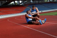 Male athelete lying on track, clasping leg in pain, another athlete helping