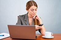 Beautiful businesswoman at desk, calling cellphone