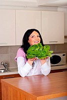 Happy brunette woman holding fresh lettuce in her kitchen