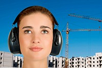 Builder pretty girl at safety earphone on a building background
