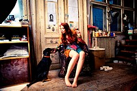 young woman wearing colorful clothes in art studio sit by the door with her dog